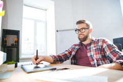 Smiling bearded designer drawing and using graphic pen tablet Stock Photography