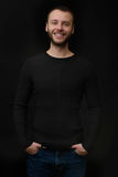 Smiling bearded dude over black background. Portrait of smiling bearded dude over black background stock photography