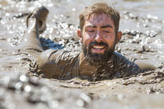 Smiling bearded face covered in mud Stock Image