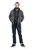 Smiling bearded hipster in jacket with hands in pockets looking at camera. Full body length portrait isolated over white studio background Royalty Free Stock Photo