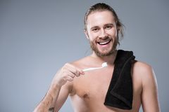 Smiling bearded man with balck towel on shoulder holding toothbrush with toothpaste in hand,. Isolated on gray Stock Images
