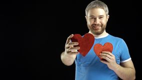 Smiling bearded man in blue tshirt giving red heart shape. Love, romance, dating, proposal concepts. Black background. 4K shot stock video