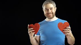 Smiling bearded man in blue tshirt holds two red heart shapes. Love, romance, dating, relationship concepts. Black stock footage