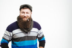 Smiling bearded man in cap and scarf with cigarette Stock Images