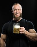Smiling Bearded man drinking beer from a beer mug over black bac Stock Photo