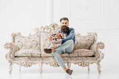 Smiling bearded man with flowers royalty free stock images