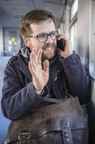 Smiling bearded man in glasses sits in a departing train and wav Royalty Free Stock Photo