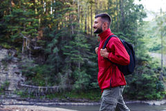 Smiling bearded man hiking along mountains river. Side view of smiling bearded man with backpack hiking along mountains river Stock Images