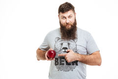 Smiling bearded man holding an apple and pointing on it Stock Photo