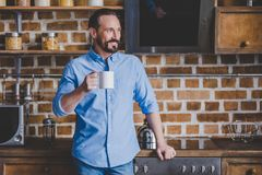 Man holding coffee cup. Smiling bearded man holding coffee cup and looking away at the kitchen Royalty Free Stock Image