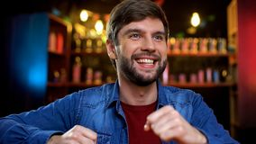 Smiling bearded man rejoicing national sports team victory in game at pub. Stock photo stock images