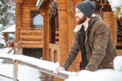 Smiling bearded man standing near wooden cottage in winter Stock Image