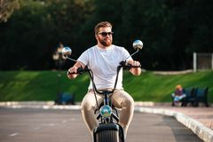 Smiling bearded man in sunglasses rides on modern motorbike Stock Photos