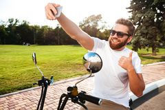 Smiling bearded man in sunglasses sitting on modern motorbike Stock Images