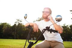 Smiling bearded man in sunglasses sitting on modern motorbike Royalty Free Stock Image