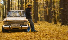 Smiling bearded man with a tattoo stands near a retro car in an autumn forest stock image