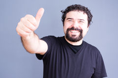 Smiling bearded man with thumb up. Middle aged bearded single man in black shirt sticking his hand outward with thumb up and big happy smile over gray background Stock Photos