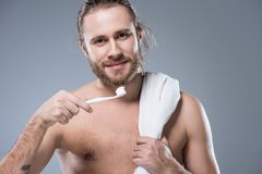 Smiling bearded man with towel on shoulder holding toothbrush with toothpaste in hand,. Isolated on gray Stock Photo