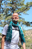 Smiling bearded man, traveler stands in the mountains Stock Images