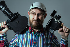 Smiling bearded man two old retro film camera Stock Image