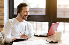 Smiling bearded man using gadgets in the cafe Royalty Free Stock Photography