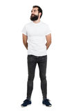 Smiling bearded man wearing white t-shirt and tight jeans looking away. Royalty Free Stock Photo