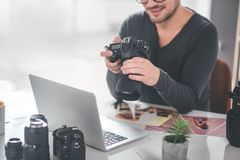Male hand holding appliance for photos. Smiling bearded men keeping professional camera while sitting at table in office. Labor concept. Copy space Stock Images