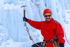 Positive climber with ice ax on glacier background stock photo