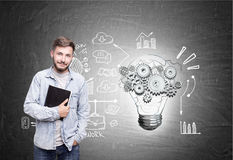 Smiling bearded student and a bulb with cogs. Portrait of a cheerful young man with a copybook standing near a chalkboard with a light bulb with cogs and a Royalty Free Stock Photography
