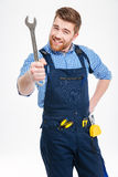 Smiling bearded young man standing and showing wrench Royalty Free Stock Photos
