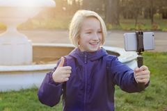 Smiling beatiful preteen girl 9-11 year old taking a selfie outdoors. Child taking a self portrait with mobile phone stock image
