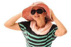 Smiling beautiful adult woman adjusting retro straw sun hat Royalty Free Stock Image