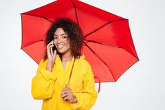 Smiling beautiful african woman in raincoat hiding under umbrella Royalty Free Stock Photo