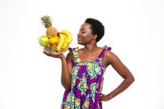 Smiling beautiful african woman standing and posing with exotic fruits Royalty Free Stock Photography