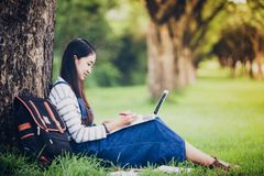 Smiling beautiful Asian girl reading book and working at tree on royalty free stock photography