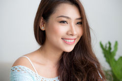 Smiling beautiful asian woman relaxing in the morning sitting by Royalty Free Stock Photography