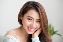 Smiling beautiful asian woman relaxing in the morning sitting by Stock Photography