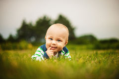 Smiling beautiful baby looking at camera outdoors in sunlight Royalty Free Stock Images
