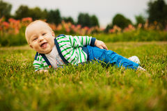 Smiling beautiful baby looking at camera outdoors in sunlight. Smiling baby looking at camera outdoors in sunlight, wearing stripped cardigan ang blue pants Stock Images