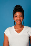 Smiling beautiful black woman. Wearing a white shirt against a simple blue background with room for text Royalty Free Stock Photo