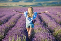Smiling beautiful blond lady model on lavender field enjoy summer day wearing airy whit dress with bouquet of flowers stock images