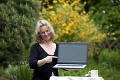 Smiling beautiful blond woman pointing at laptop. A smiling beautiful mature blond woman sitting in her garden presenting her laptop and pointing at it Stock Photo