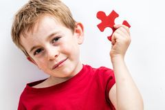 Smiling beautiful boy with freckles finding jigsaw for unique solution stock photos