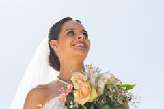 Smiling beautiful bride with bouquet against clear sky Royalty Free Stock Images