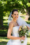 Smiling beautiful bride with bouquet standing in park Royalty Free Stock Photography