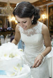 Smiling beautiful bride cutting the wedding cake Royalty Free Stock Photo