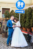 Smiling beautiful bride with rose bouquet and handsome groom in blue suit embracing under the sign kiss place Royalty Free Stock Image