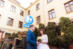 Smiling beautiful bride with rose bouquet and handsome groom in blue suit embracing under the sign kiss place Stock Image