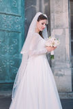 Smiling beautiful bride on your wedding day with big bouquet near church. Green Old Door. Stock Images