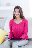 Smiling beautiful brunette doing online shopping on the couch Royalty Free Stock Image